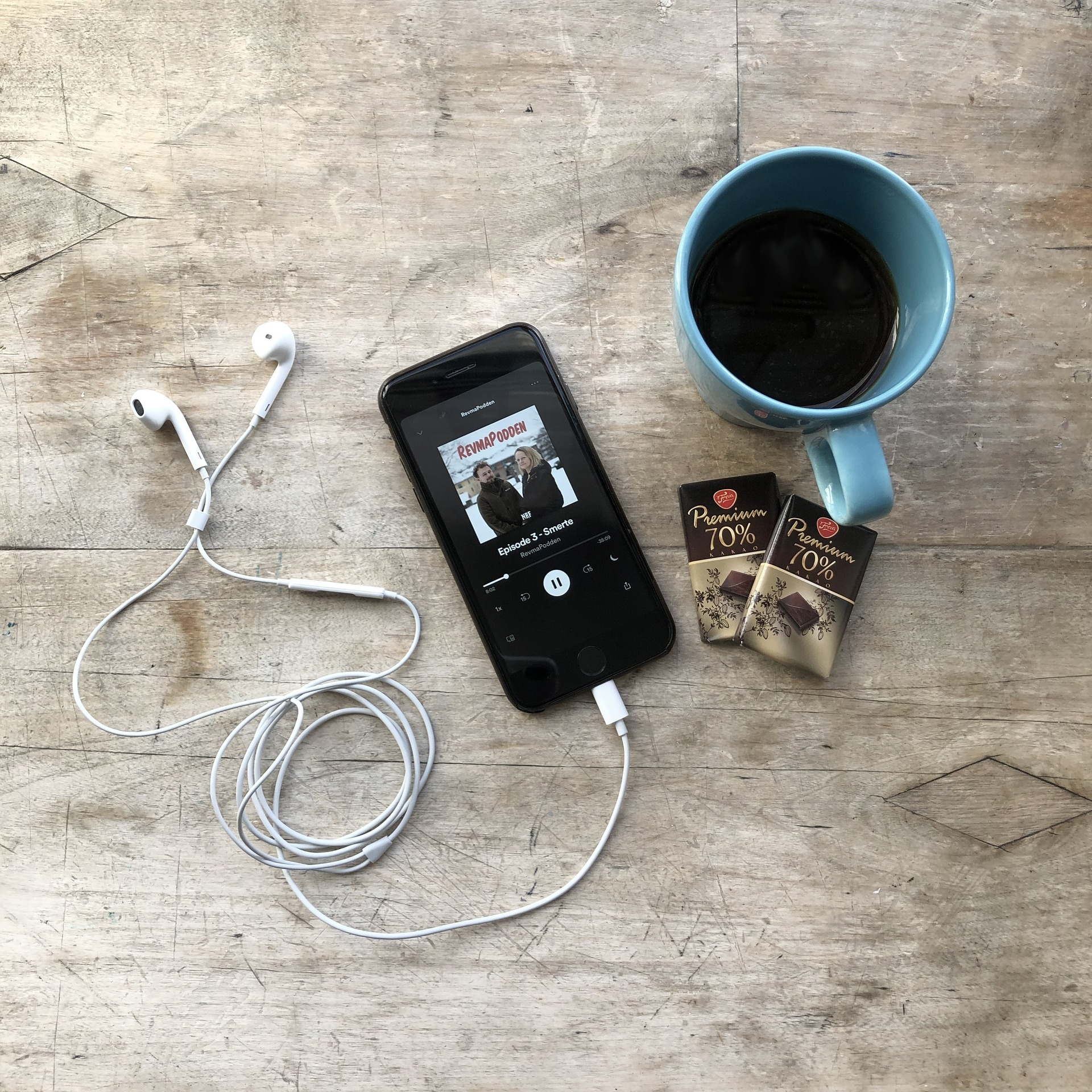 Phone with headphones, chocolate and a blue cup