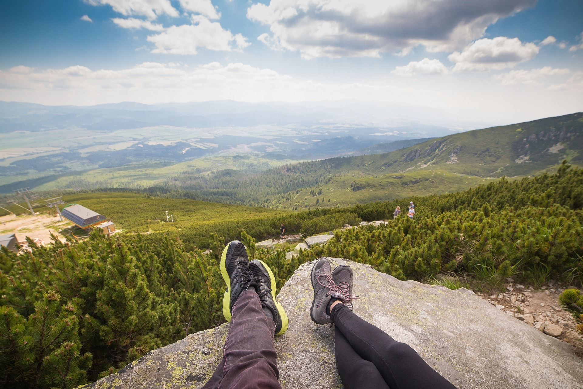 Two sets of feet with legs on a boulder with a view of vast trees in the distance
