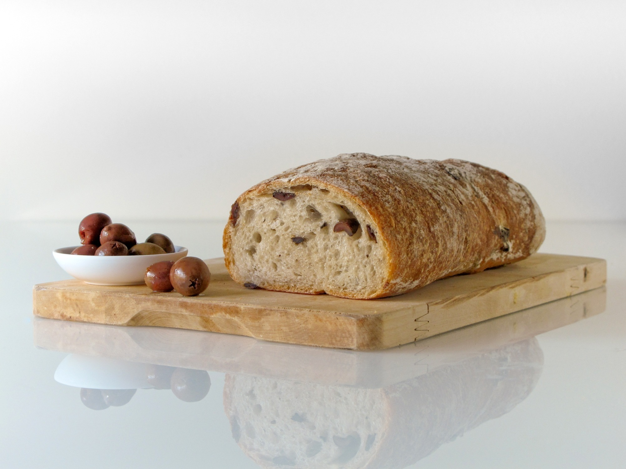 Load of bread on board with side of olives