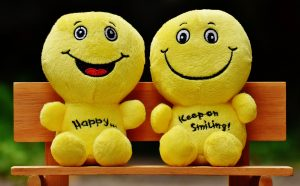 Two yellow happy plush dolls sitting on bench