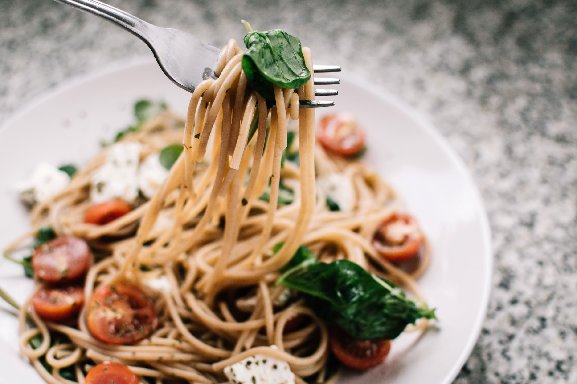 plate of pasta with basil leaves and tomatoes
