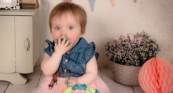 Balanced Eating: Baby Holding Hand with Cake Icing over her Mouth with a cake in front of her.