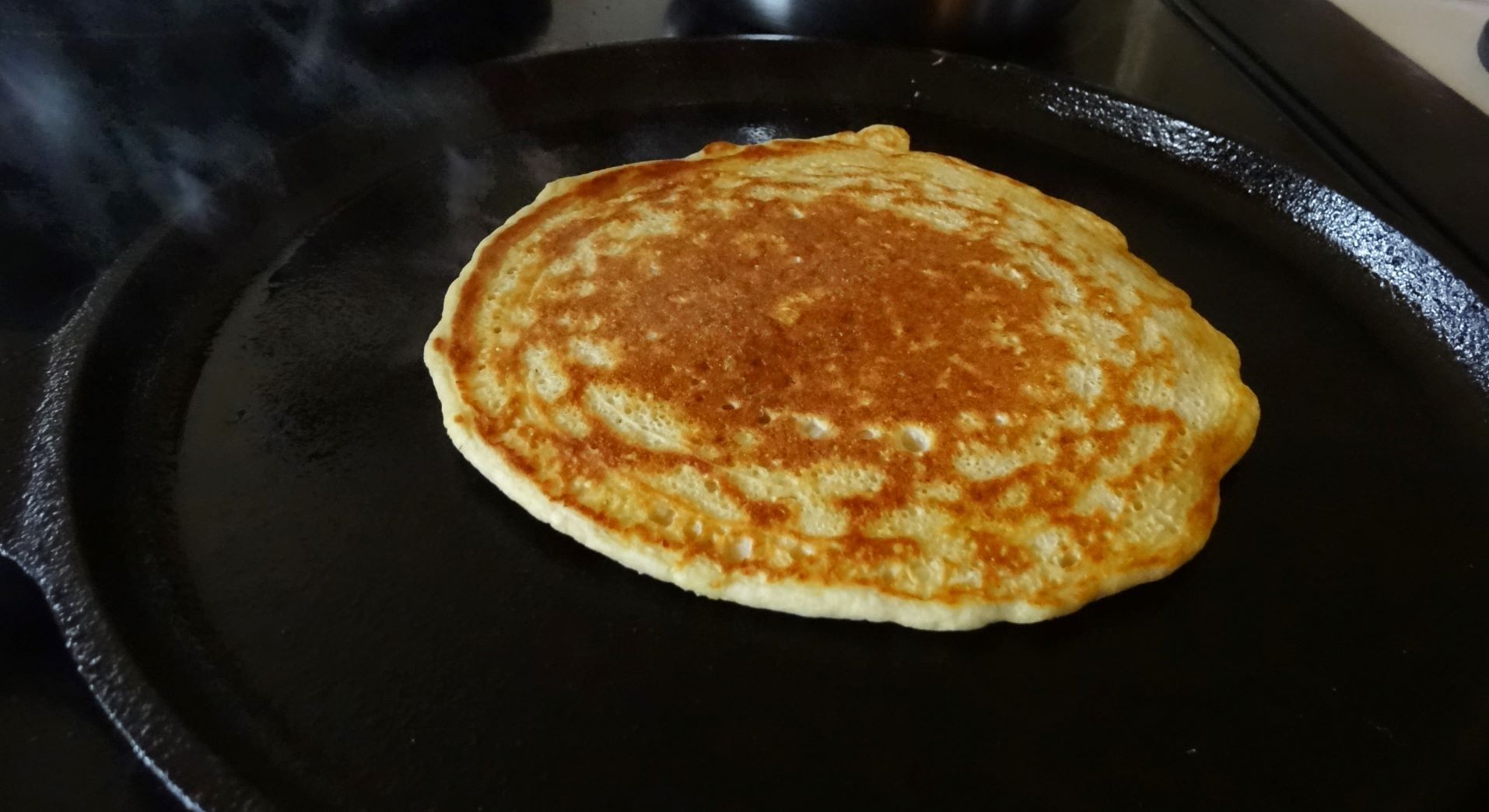 Golden brown pancake in a cast iron skillet