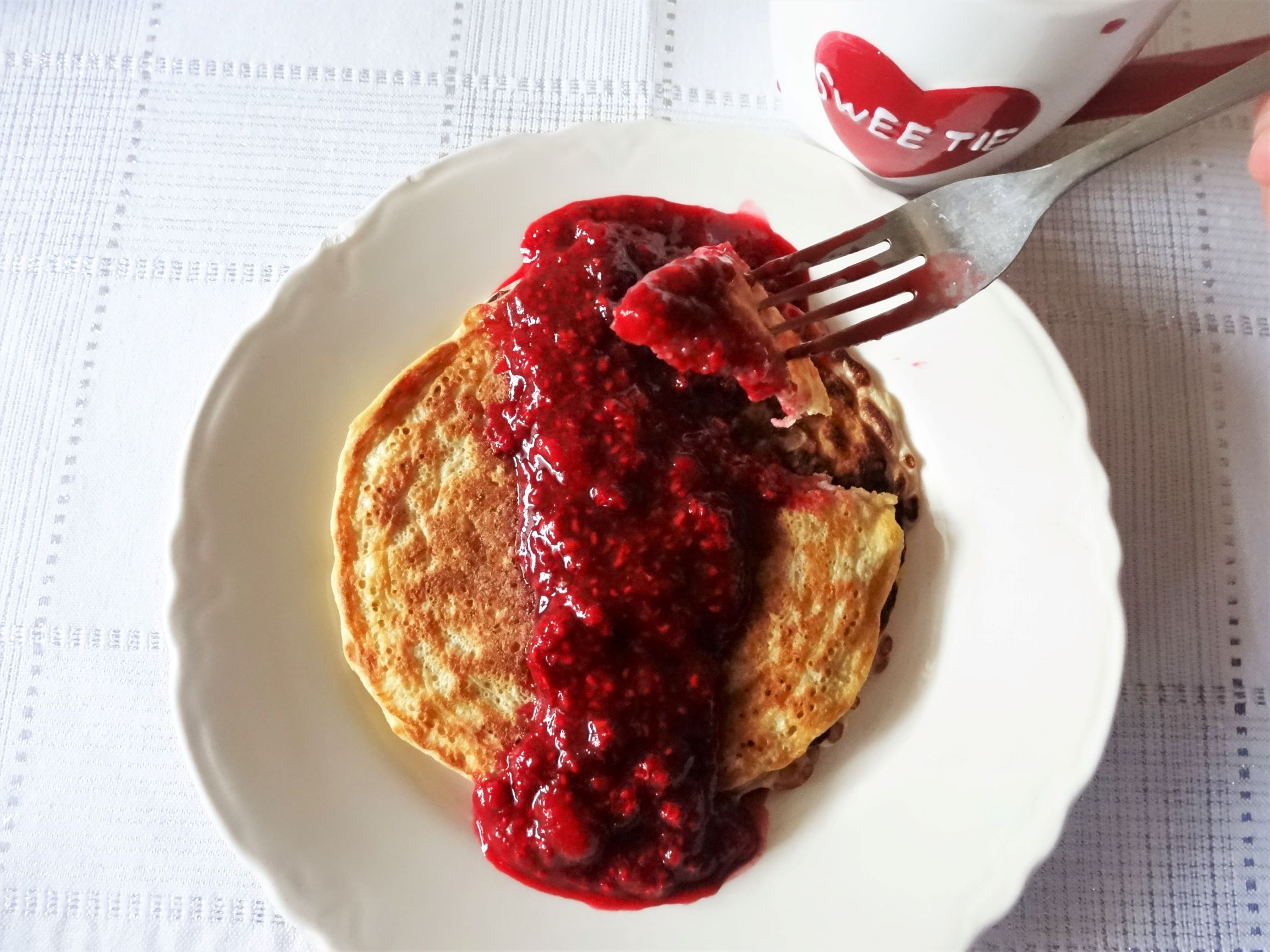 Me Oatmeal Pancakes with Raspberry Syrup, Fork and Hug Me Coffee Cup